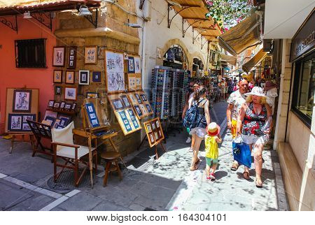 Rethymnon, Island Crete, Greece - July 1 2016: People and tourists walking on the narrow street of Rethymnon (part of Old Town) and buying souvenirs