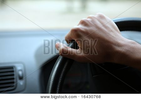 Close-up of a male hand on steering wheel in a modern car in the UK (steering wheel on the right)