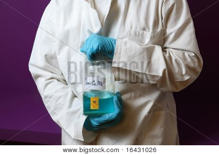 male scientist wearing protective gloves holding a toxic blue chemical in front of a violet wall