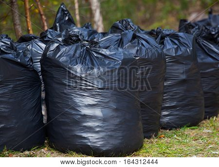 Black complete and tied garbage bags standing together on the street outdoors. removal sorting and recycling rubbish.