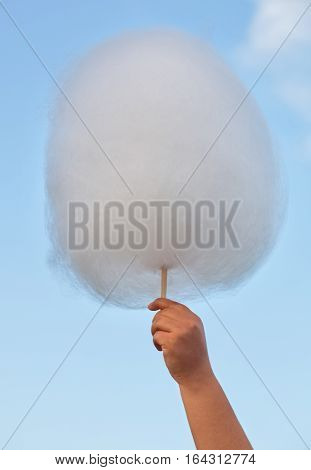 A child at the fair keeps bought cotton candy in hand on background of cloudy sky.