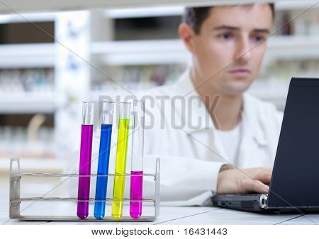 portrait of a young male researcher working on a laptop computer while carrying out research in a lab (the focus is on the test tubes in the foreground; color toned image)