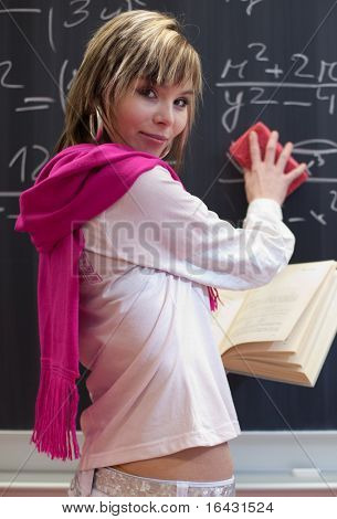 pretty young college student erasing the error she has just made in a math equation on chalkboard/blackboard in a classroom