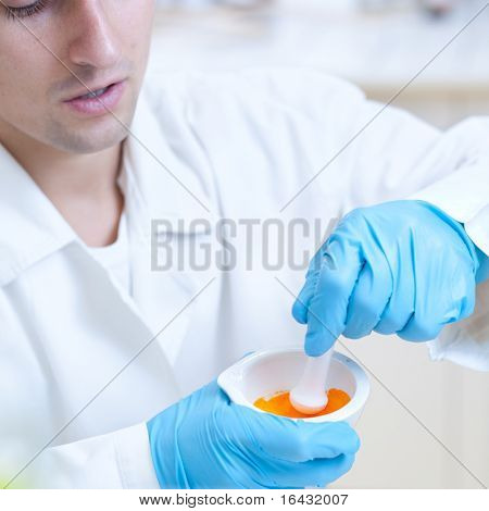 portrait of a young male researcher using a mortar and a pestle to homogenize a mixture while working in a lab