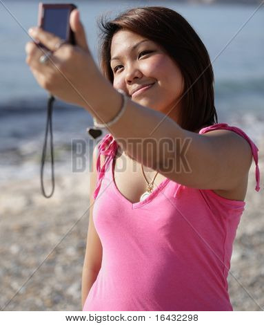 Pretty young asian woman taking a self-portrait while outdoors on a beach on a summer day