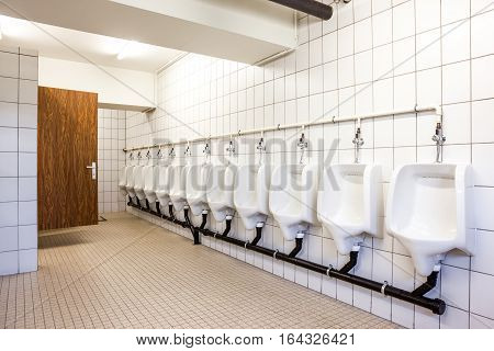 urinals and toilet doors in an old building for men only