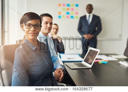 Grinning Woman Seated With Colleagues In Meeting