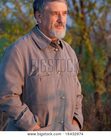 Portrait of a handsome senior man standing outdoors in warm evening light