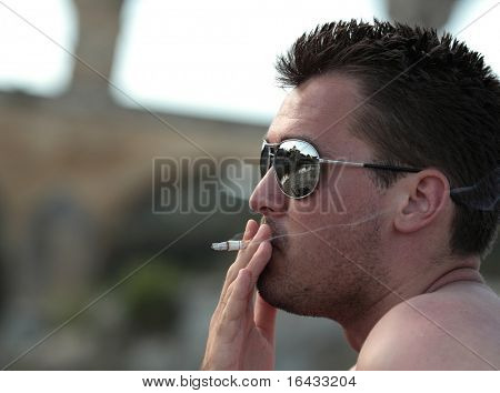 Deadly nasty habit - Male smoker wearing sunglasses smoking a cigarette outdoors