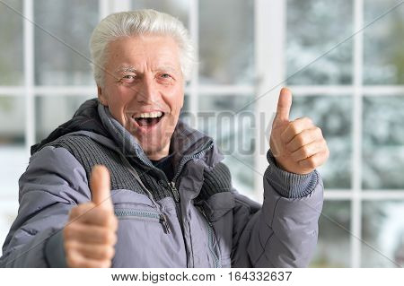 Portrait of a happy mature man with thumb ups