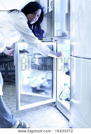 Portrait of a female researcher carrying out research experiments in a lab - researcher taking a substance from a freezer (color toned image)
