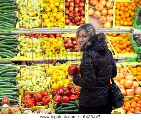 Beautiful young woman shopping for fruits and vegetables at a supermarket