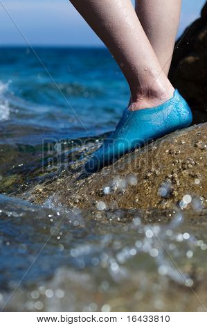 close-up of a young woman's feet wearing swim shoes while on a rocky beach