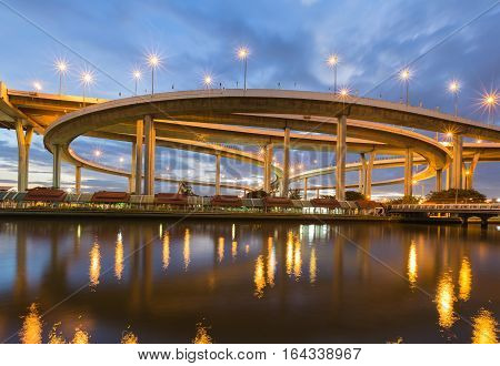 Night round about highway intersection with twilight sky background and reflection on the river Bangkok Thailand
