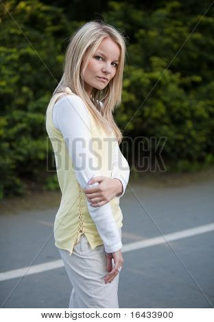 portrait of a pretty young blonde woman in a park
