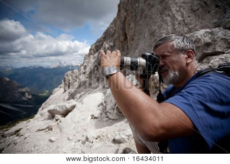 handsome senior male photographer in high mountain setting taking pictures