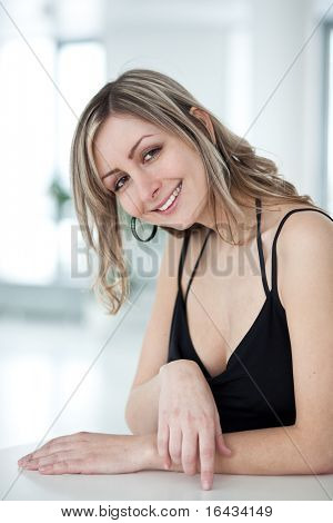 portrait of a very pretty young woman wearing nice black dress, smiling , looking at you