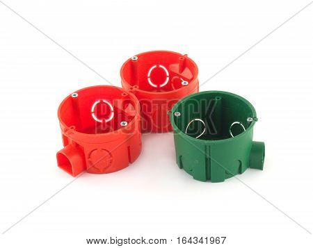 Three color plastic containers for electric wire mounting isolated on white closeup