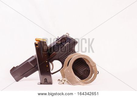 Pistol, clip and handcuffs with a white background.
