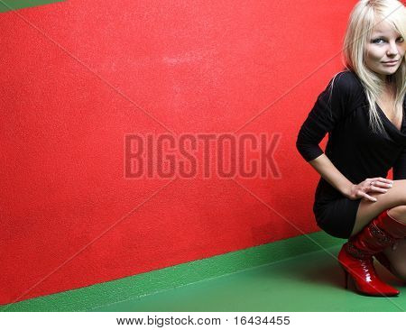 young and pretty blonde female photo model posing in front of a red wall