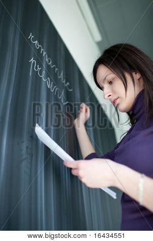 bastante joven estudiante escribiendo en la pizarra durante una clase de literatura