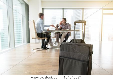 Close up of suitcase in real estate agency, young couple got help with mortgage interest, signed contract for a long-term housing, told about housing options of young people, renting apartment on trip