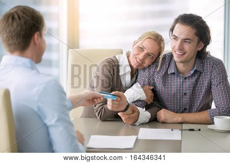 Young happy couple getting a loan concept, first time home buyers, tenancy agreement, agency as a broker between the landlord and tenant, signed all paper and paying with credit card
