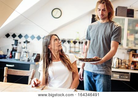 Young man serving a burnt pizza for lunch. While he seems quite proud of his cooking success, his girlfriend looks rather skeptical.