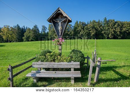 wooden wayside shrine with crucified jesus figure and resting bench bavaria