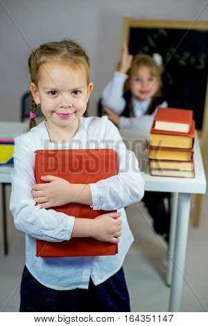 Two Young Schoolgirls With Red Textbooks