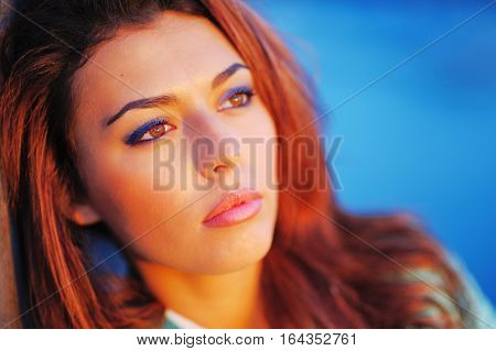 Portrait of young beautiful pensive woman with copper-brown hair in the bright rays of setting sun close up.