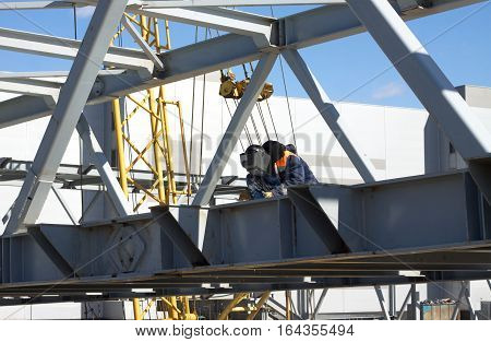 Electric welding worker welds metal structures in the construction of industrial object