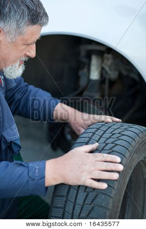 mechanic changing a wheel of a modern car (color toned image)