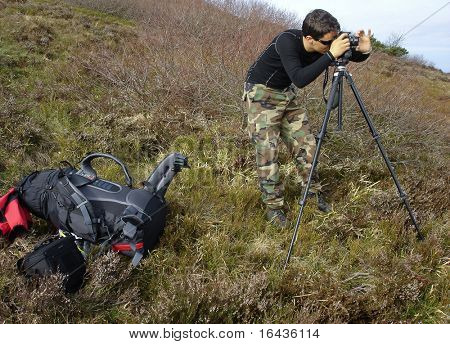 handsome young photographer taking landscape photos outdoors