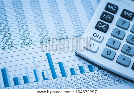 Accounting financial banking stock spreadsheet data with calculator in blue.