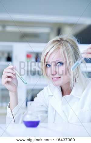 Closeup of a female researcher holding test tubes with chemicals while carrying out some experiments in a laboratory (color toned image)