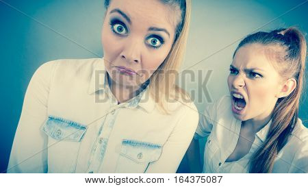 Conflict bad relationships friendship difficulties. Two young women having argument. Angry fury girl screaming at her friend or younger sister