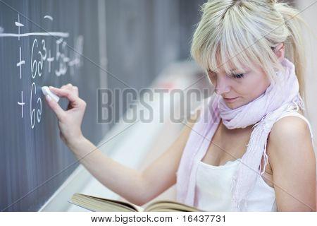 bastante joven estudiante escribiendo en la pizarra/pizarra durante una clase de matemáticas (color tonos i