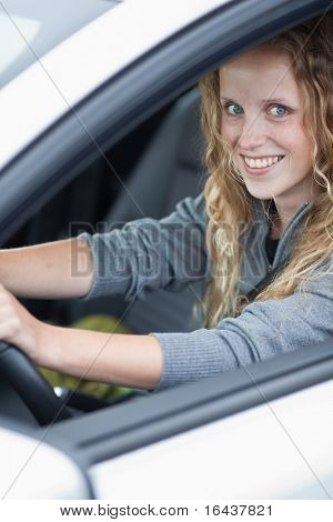 Pretty young woman driving her new car (color toned image)