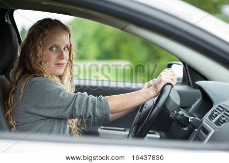 Pretty young woman driving her brand new car (color toned image)