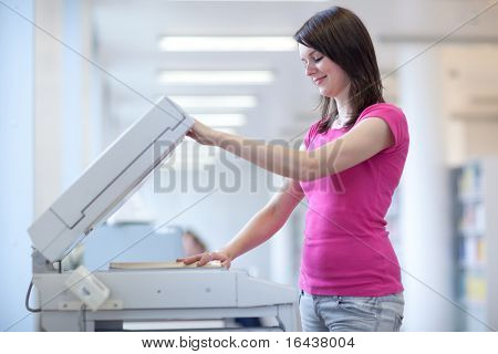 pretty young secretary using a copy machine (shallow DOF; color toned image)