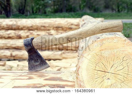 Axe stuck in a log closeup. Construction of rural house from planed heavy logs. Horizontal photo