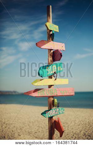 Wooden handmade signpost on the tropic beach.