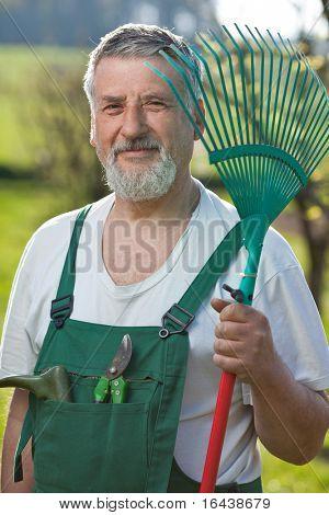 Portrait of a handsome senior man gardening in his garden (color toned image)