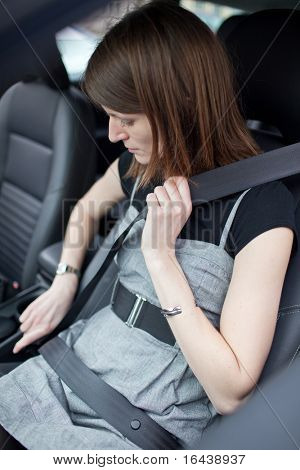 Road safety concept - Pretty young woman fastening her seat belt in a car
