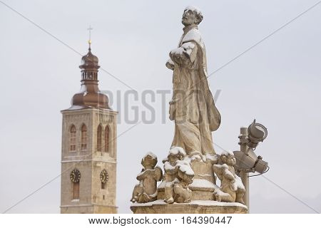 Historical statue and tower of St. James church in town Kutna Hora Czech republic snow floodlight