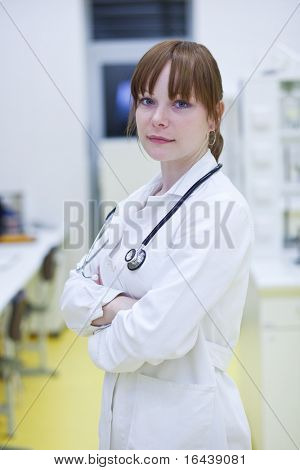 Portrait of a successful young female doctor in a hospital lab, looking confident (color toned image)