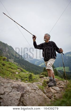 handsome senior man showing direction with his hiking stick while hiking outdoors in mountains