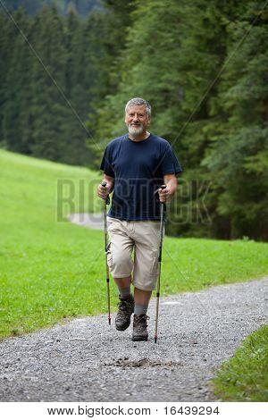 activo guapo senior nordic walking al aire libre en un sendero de bosque, disfrutando de su retiro