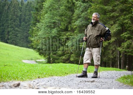 active handsome senior man stoping for a moment while nordic walking/hiking outdoors on a forest path, enjoying his retirement
